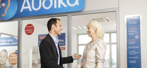 Audiprothésiste et client devant centre audika